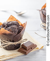 Homemade muffins with chocolate on wooden table. Vertical view