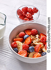 Homemade natural breakfast with granola, strawberries, almonds, blueberries, raspberry, fresh soy milk in a bowl on a wooden background