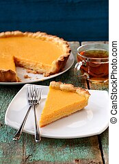 Homemade old fashioned pumpkin pie and black tea on old table painted pale blue