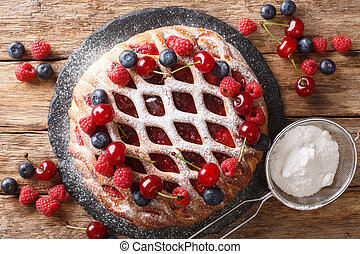 Homemade open Berry pie with raspberries, blueberries and cherries close-up on a slate board. horizontal top view