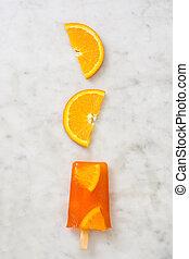 Homemade orange popsicle on marble