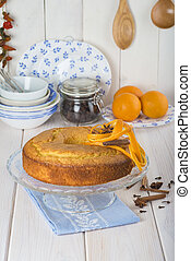 Homemade orange sponge cake on a glass cake stand over the ...