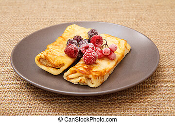 Homemade pancakes filled with cottage cheese and topped with frozen raspberries