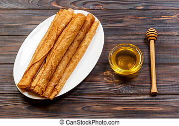 Homemade pancakes with honey on white plate, dipper, wooden table. top view. copy space