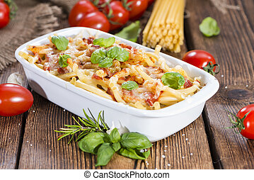 Portion of homemade Pasta Bake (with Macaroni) on wooden background