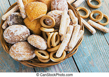 Homemade pastries in a wicker basket on a wooden background