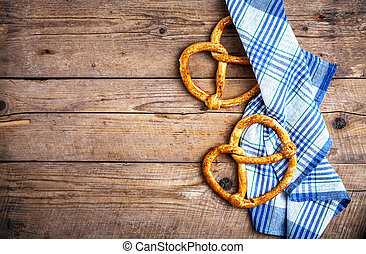 Homemade pastries. Pretzel with kitchen towel on wooden background. Food