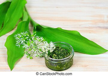 Homemade pesto in a jar with wild garlic flower and leaves.