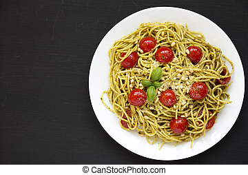 Homemade Pesto Pasta with Tomatoes and Pine Nuts on a black background, top view. Flat lay, overhead, from above. Copy space.