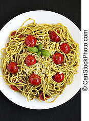Homemade Pesto Pasta with Tomatoes and Pine Nuts on a black background, top view. Flat lay, overhead, from above. Close-up.