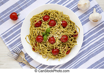 Homemade Pesto Pasta with Tomatoes and Pine Nuts on a white plate, overhead view. Flat lay, top view, from above.