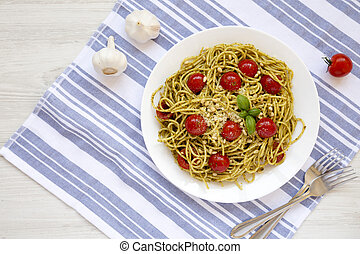 Homemade Pesto Pasta with Tomatoes and Pine Nuts on a white plate, overhead view. Flat lay, top view, from above. Space for text.