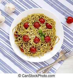 Homemade Pesto Pasta with Tomatoes and Pine Nuts on a white plate, top view. Flat lay, from above.