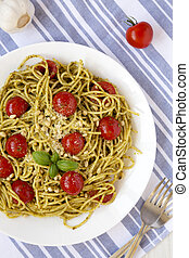 Homemade Pesto Pasta with Tomatoes and Pine Nuts on a white plate, top view. Flat lay, overhead, from above.