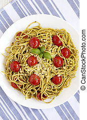 Homemade Pesto Pasta with Tomatoes and Pine Nuts on a white plate, top view. Flat lay, overhead, from above. Close-up.