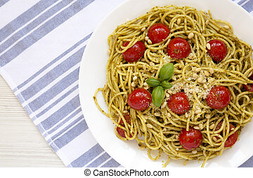Homemade Pesto Pasta with Tomatoes and Pine Nuts on a white plate, top view. Flat lay, overhead, from above. Copy space.