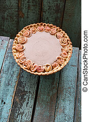 Homemade pie with cream filling and apple roses on old wooden blue background