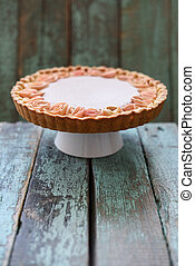 Homemade pie with cream filling and apple roses on stand on wooden blue background