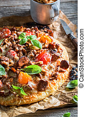 Homemade pizza made of noble mushrooms and tomatoes