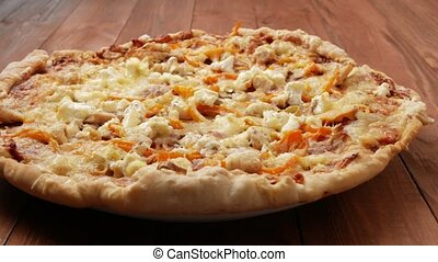 Homemade pizza with different sorts of cheese and tomatoes on a wooden table. Moving camera