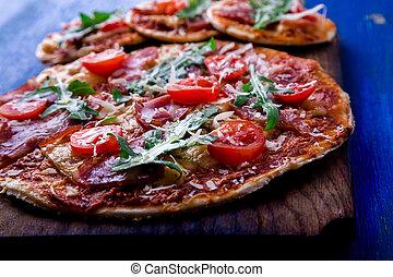 Homemade pizza with prosciutto, tomato, arugula on wooden board blue background.