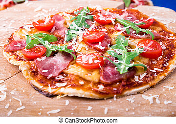 Homemade pizza with prosciutto, tomato, arugula on wooden board blue background