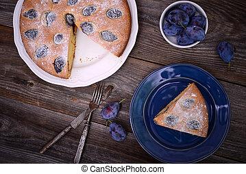 Homemade plum cake on wooden background
