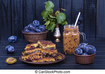 Homemade plum pie in plate, plum smoothies and raw blue plums on black wooden background,