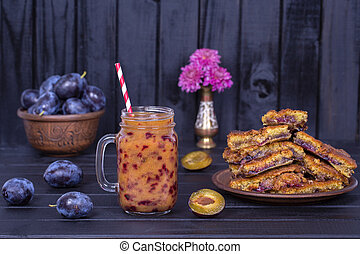 Homemade plum pie in plate, plum smoothies and raw plums on black wooden background