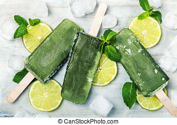 Homemade popsicles with kiwi and lemon on a wooden table