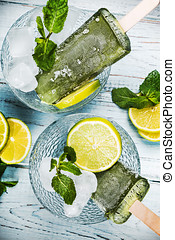 Homemade popsicles with lime and mint on a wooden table