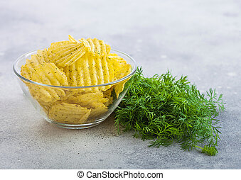 Homemade potato crisp chips inside glass bowl with fresh raw dill on light board background.