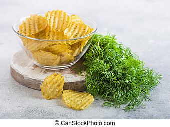 Homemade potato crisp chips inside glass bowl with fresh raw dill on white board table background.