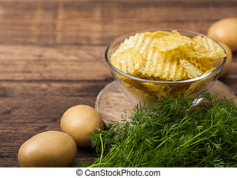 Homemade potato crisp chips inside glass bowl with fresh raw dill on wooden background and raw potatoes.