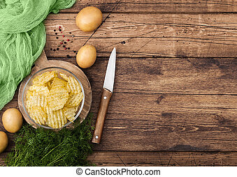 Homemade potato crisp chips inside glass bowl with fresh raw dill on wooden background and raw potatoes and knife.