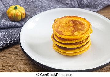 Homemade pumpkin pancakes on the white plate.