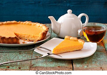 Homemade pumpkin pie and black tea on old table painted blue