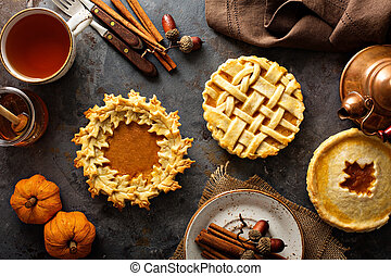 Homemade pumpkin pies decorated with fall leaves overhead