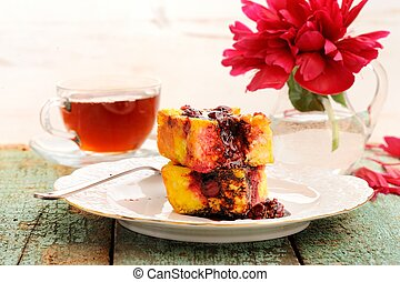 Homemade quark pie with cherries, black tea and red peony on old wooden background