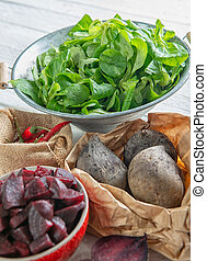 homemade raw beetroot salad in small bowl with green salad