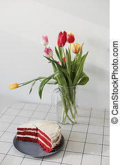 homemade red velvet cake and a bouquet of tulips in a glass vase