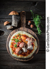 Homemade rustic pizza with noble mushrooms and herbs