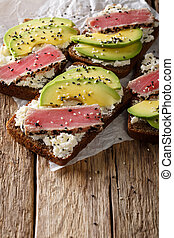 Homemade sandwiches with tuna steak in sesame, avocado and cream cheese close-up. vertical
