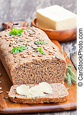 Homemade sliced rye bread with sunflower seeds and fresh butter