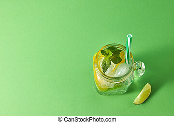 Homemade sparkling cold alcoholic mojito from natural citrus fruits with plastic straws on a green background. Top view. Copy space.