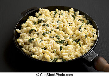 Homemade Spinach Mac and Cheese in a cast-iron pan on a black background, side view. Close-up.