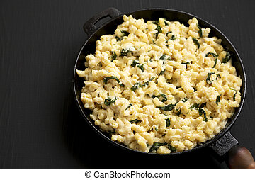 Homemade Spinach Mac and Cheese in a cast-iron pan on a black background, side view. Space for text.