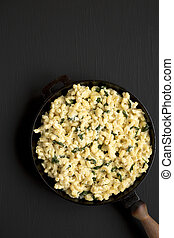Homemade Spinach Mac and Cheese in a cast-iron pan on a black background, top view. Flat lay, overhead, from above. Copy space.