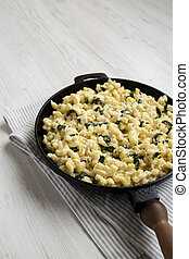 Homemade Spinach Mac and Cheese in a cast-iron pan on a white wooden surface, side view. Copy space.