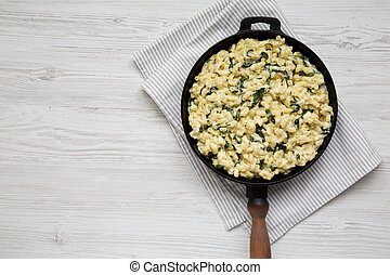 Homemade Spinach Mac and Cheese in a cast-iron pan on a white wooden surface, top view. Flat lay, top view, from above.